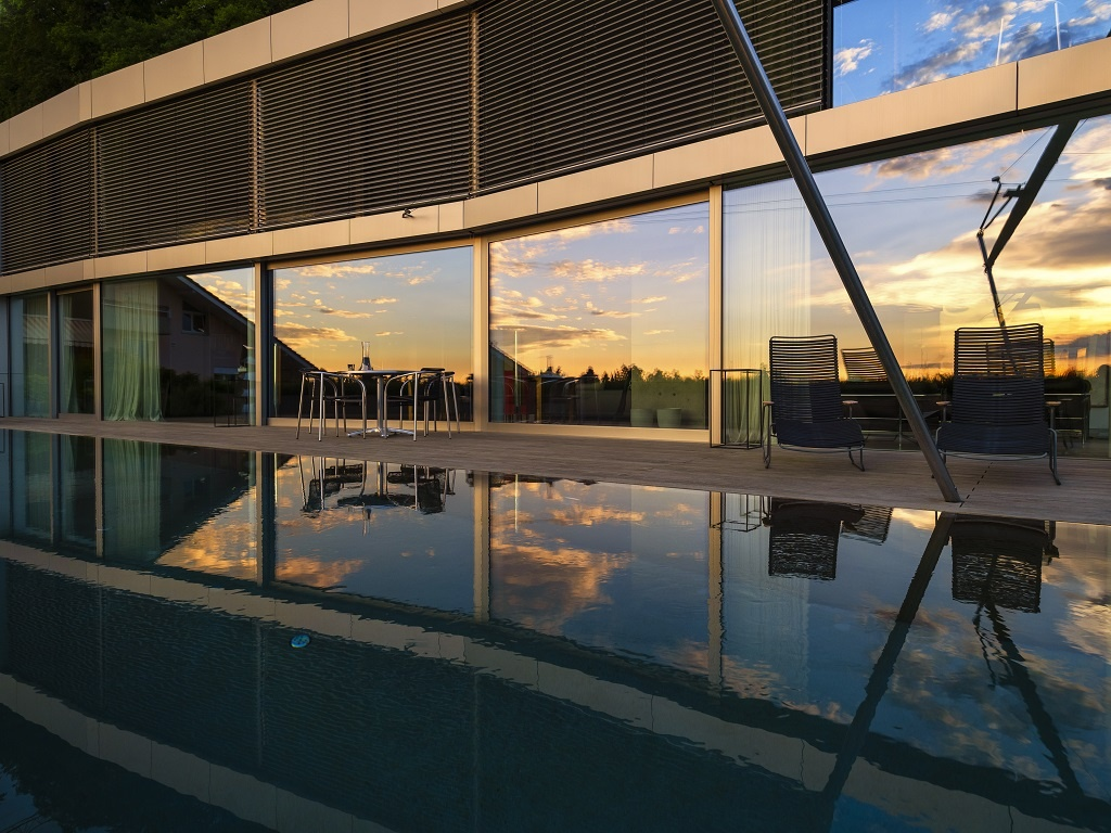 Switzerland, glass front of modern villa at dusk with terrace and pool in the foreground